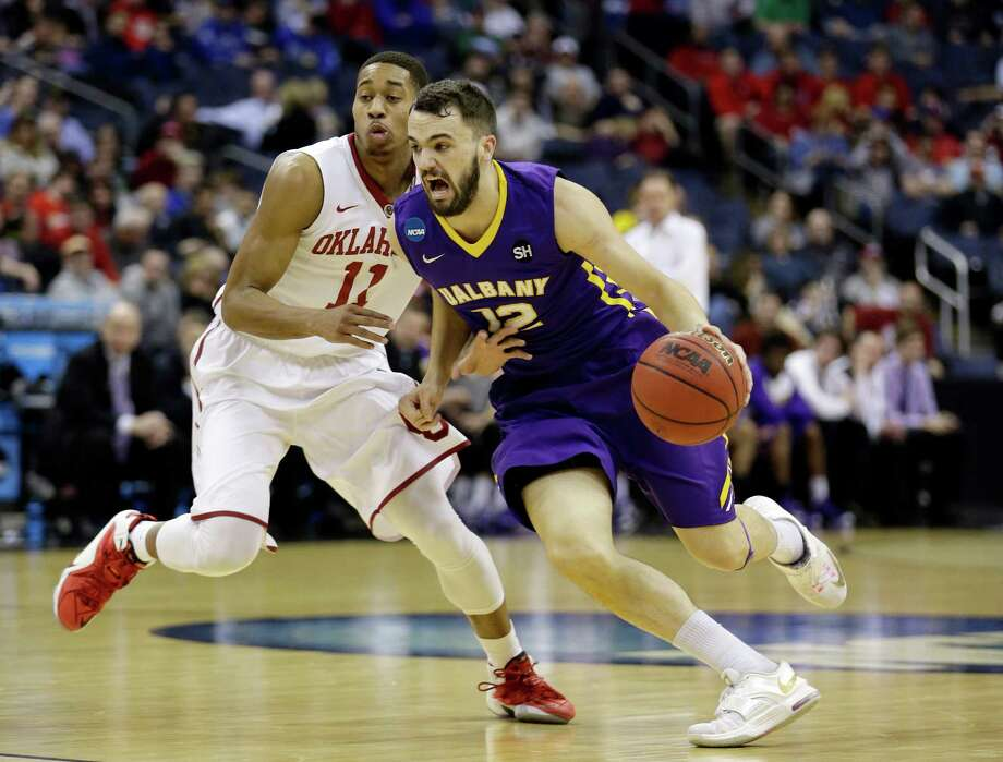 Albany's Peter Hooley (12), from Australia, drives past Oklahoma's Isaiah Cousins (11) in the first half of an NCAA tournament college basketball game in the Round of 64 in Columbus, Ohio, Friday, March 20, 2015. (AP Photo/Tony Dejak) ORG XMIT: OHMD160 Photo: Tony Dejak / AP