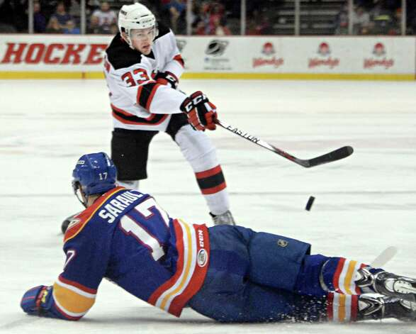 Albany Devils's #33 Corbin McPherson, top, blasts the puck over Norfolk Admirals #17 Charles Sarault during Saturday's game at the Times Union Center  March 21, 2015 in Albany, NY.  (John Carl D'Annibale / Times Union) Photo: John Carl D'Annibale / 00030124O