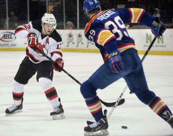 Albany Devils's #12 Tim Sestito, left, shoots a pass between the legs of Norfolk Admirals #39 Dave Steckel during Saturday's game at the Times Union Center  March 21, 2015 in Albany, NY.  (John Carl D'Annibale / Times Union) Photo: John Carl D'Annibale / 00030124O