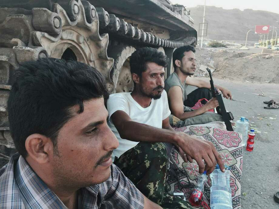Members of a militia group loyal to Yemen's President Abed Rabbo Mansour Hadi, known as the Popular Committees, chew qat, Yemen's favorite drug, as they sit next to their tank, guarding a major intersection in Aden, Yemen, Saturday, March 21, 2015. Yemen's Shiite rebels issued a call to arms Saturday to battle forces loyal to the embattled President Hadi, as U.S. troops evacuated a southern air base over al-Qaida militants seizing a nearby city, authorities said. (AP Photo/Hamza Hendawi) Photo: Hamza Hendawi, STF / Associated Press / AP