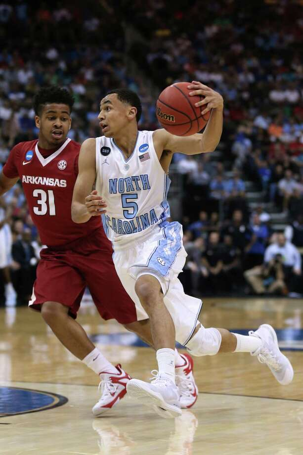 JACKSONVILLE, FL - MARCH 21:  Marcus Paige #5 of the North Carolina Tar Heels dribbles past Anton Beard #31 of the Arkansas Razorbacks in the first half during the third round of the 2015 NCAA Men's Basketball Tournament at Jacksonville Veterans Memorial Arena on March 21, 2015 in Jacksonville, Florida.  (Photo by Mike Ehrmann/Getty Images) ORG XMIT: 527065515 Photo: Mike Ehrmann / 2015 Getty Images