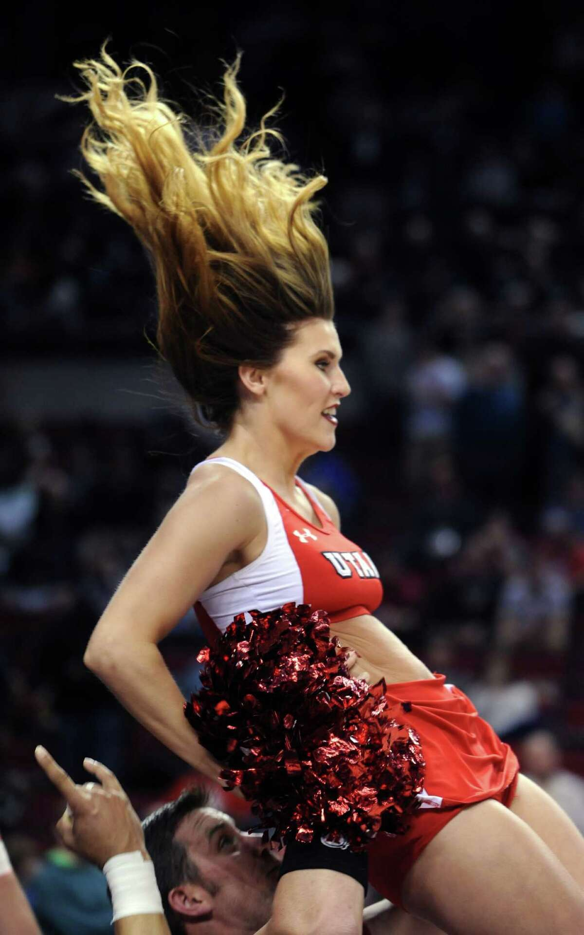A Utah cheerleaders' hair flies during a routine in the first half of an NCAA college basketball tournament round of 32 game against Georgetown in Portland, Ore., Saturday, March 21, 2015.