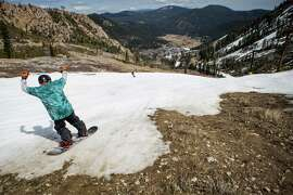 A snowboarder threads his way through patches of dirt at Squaw Valley Ski Resort in Olympic Valley. Many Tahoe-area ski resorts have closed due to low snowfall as California's historic drought continues.