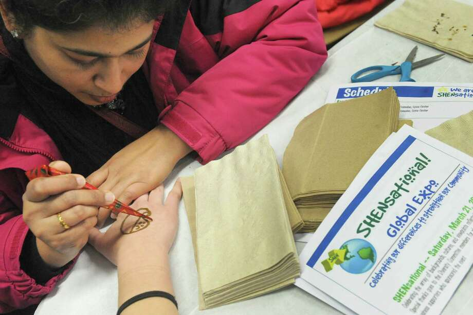 "Shen parent Kavitha Pradeep applies a henna tattoo to 14-year-old Serena Burnetter during ""Shensational""  an annual celebration of cultural diversity at Shenendehowa High School west on Saturday March 21, 2015 in Clirton Park, N.Y. (Michael P. Farrell/Times Union) Photo: Michael P. Farrell / 10031095A"