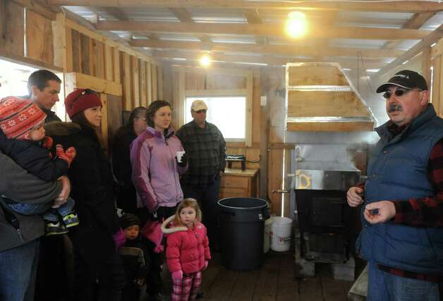 Owner Karl Ruger, right, explains the maple syrup making process in his sugar house during an open house at Sugar Oak Farms on Saturday March 21, 2015 in Malta, N.Y. (Michael P. Farrell/Times Union) Photo: Michael P. Farrell / 10031103A