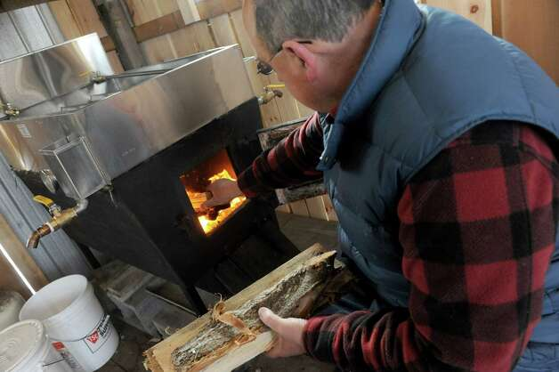 Owner Karl Ruger keeps the fire fed as he makes maple syrup in his sugar house during an open house at Sugar Oak Farms on Saturday March 21, 2015 in Malta, N.Y. (Michael P. Farrell/Times Union) Photo: Michael P. Farrell / 10031103A
