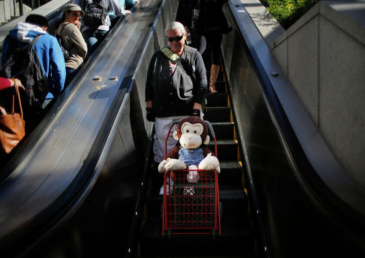 Carmella Camille and Cami, her stuffed monkey companion, head to Powell Street Muni Metro Station.