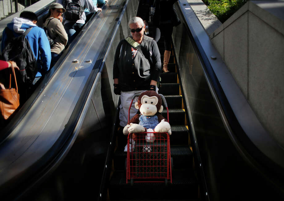 Carmella Camille and Cami, her stuffed monkey companion, head to Powell Street Muni Metro Station. Photo: Mike Kepka / The Chronicle / ONLINE_YES