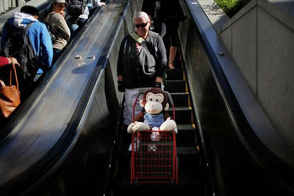 Carmella Camille and Cami, her stuffed monkey companion, head to Powell Street Muni Metro Station.