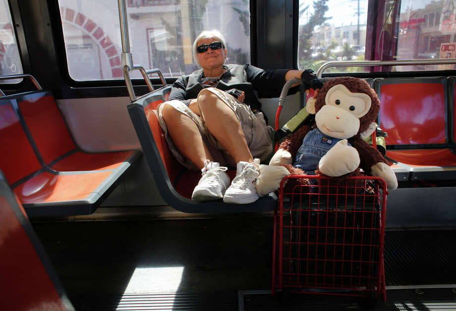 Carmella Camille and Cami, her stuffed monkey, smile as they ride the N-Judah together. Photo: Mike Kepka / The Chronicle / ONLINE_YES