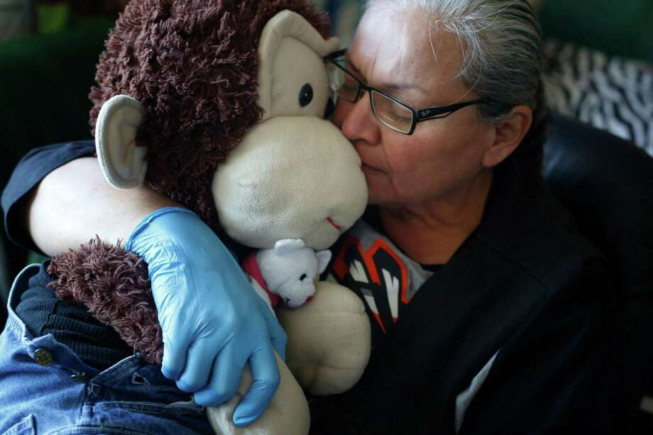 Carmella Camille hugs Cami, her stuffed monkey, at home on Wednesday March 18, 2015 in San Francisco, Calif. Camille says Cami never lets her down or hurts her. Photo: Mike Kepka / The Chronicle / ONLINE_YES