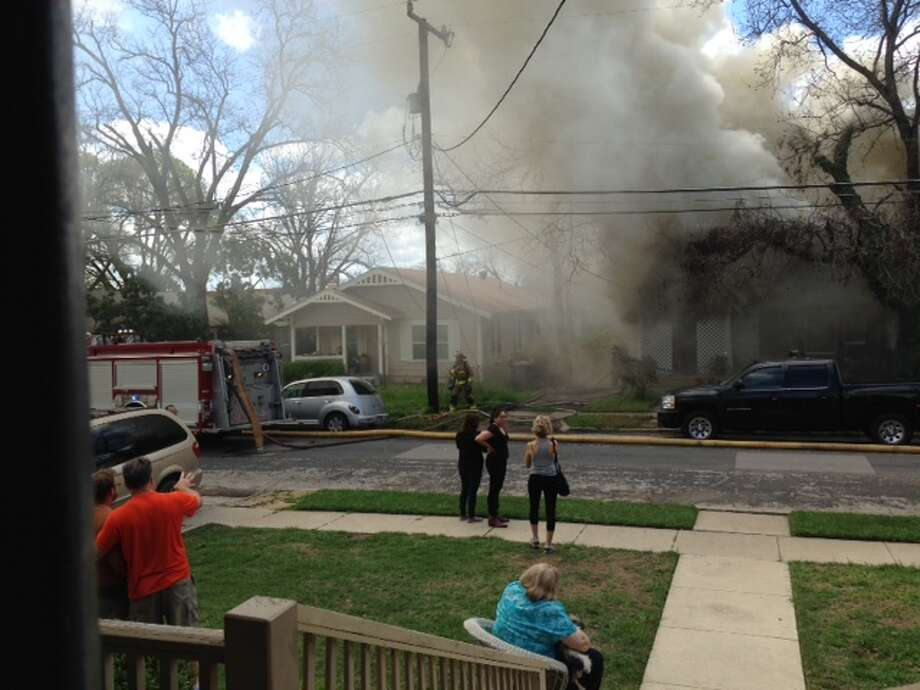 Neighbors watch as a home at at 500 E. Huisache Ave. is engulfed in smoke. The SAFD is still investigating the extent of the damage. Photo: Courtesy Photo
