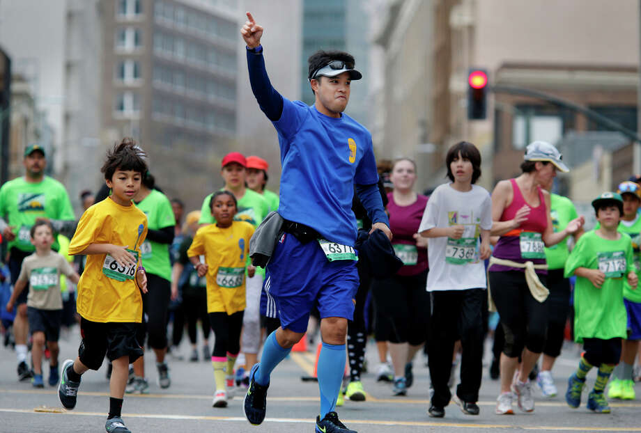 Competitors of all ages stride through the 5K in the Oakland Running Festival, a day of multiple events. Photo: Brant Ward / The Chronicle / ONLINE_YES