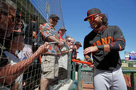 Handy with a marker as well as a glove, Brandon Crawford signs a bat for 2-year-old Vincent Mason of Bakersfield.