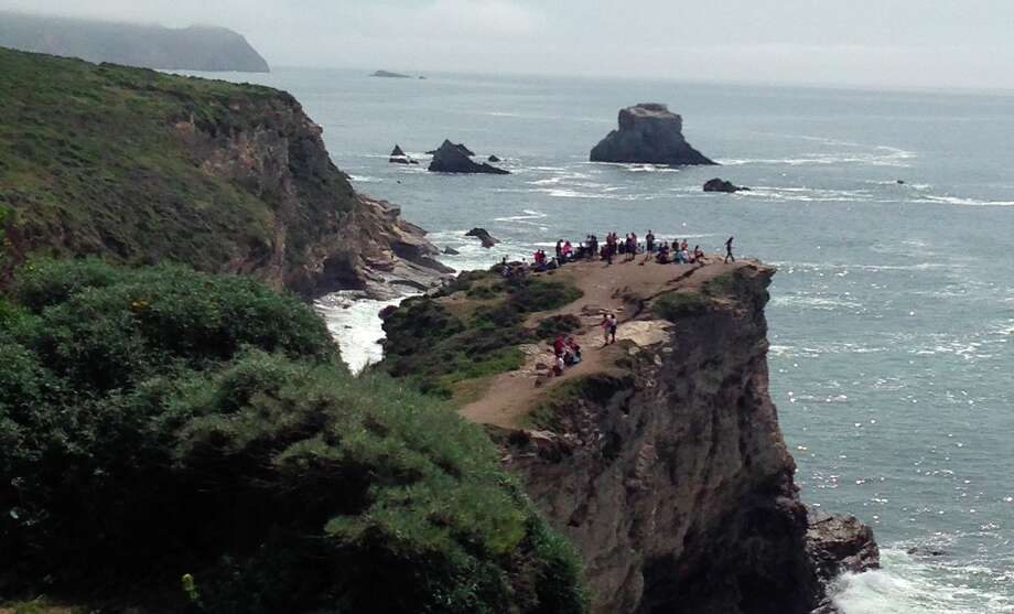 """Five hours before a cliff gave way Saturday, killing one hiker and injuring another at Point Reyes National Seashore, Karen Blasing snapped a photo of dozens of people who ventured past warning signs to the bluff overlooking Arch Rock. """"It was clear no one should be on that rock with the huge fissure,"""" she said. Photo: Karen Blasing / ONLINE_YES"""