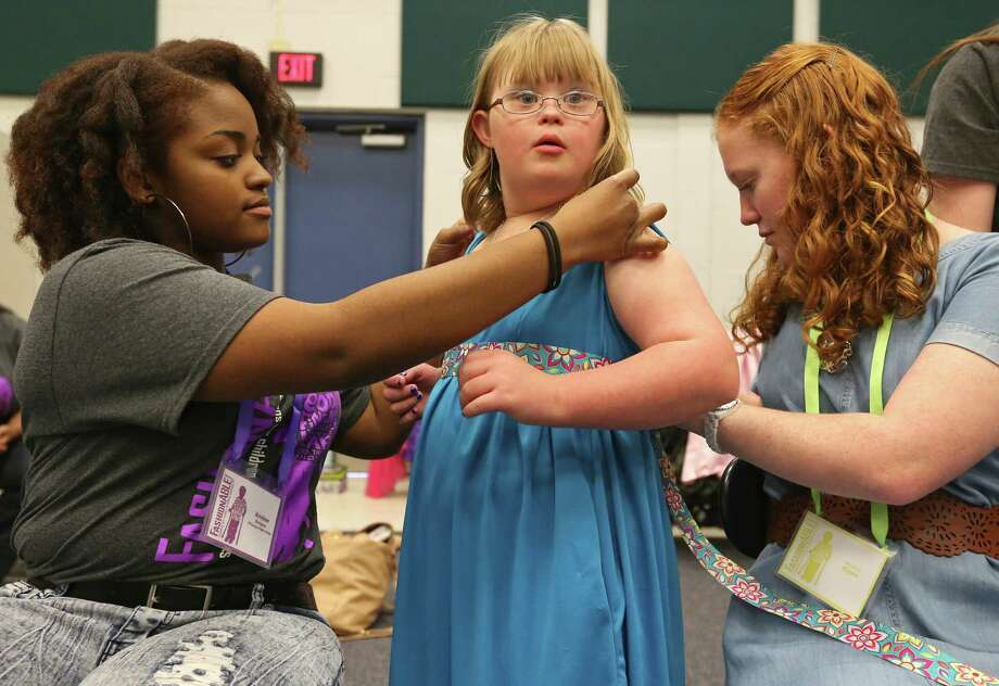 Designer O'Connor high school senior Kristian Williams, 17, (from left) adjusts model Evers elementary 5th grader Claire Graham, 10, outfit as Claire's sister Warren high school's Abbey Graham, 16, helps during the 8th annual FashionAble show held Sunday March 22, 2015 at O'Connor High School. Photo: Edward A. Ornelas, Staff / San Antonio Express-News / © 2015 San Antonio Express-News