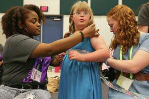 Designer O'Connor high school senior Kristian Williams, 17, (from left) adjusts model Evers elementary 5th grader Claire Graham, 10, outfit as Claire's sister Warren high school's Abbey Graham, 16, helps during the 8th annual FashionAble show held Sunday March 22, 2015 at O'Connor High School.