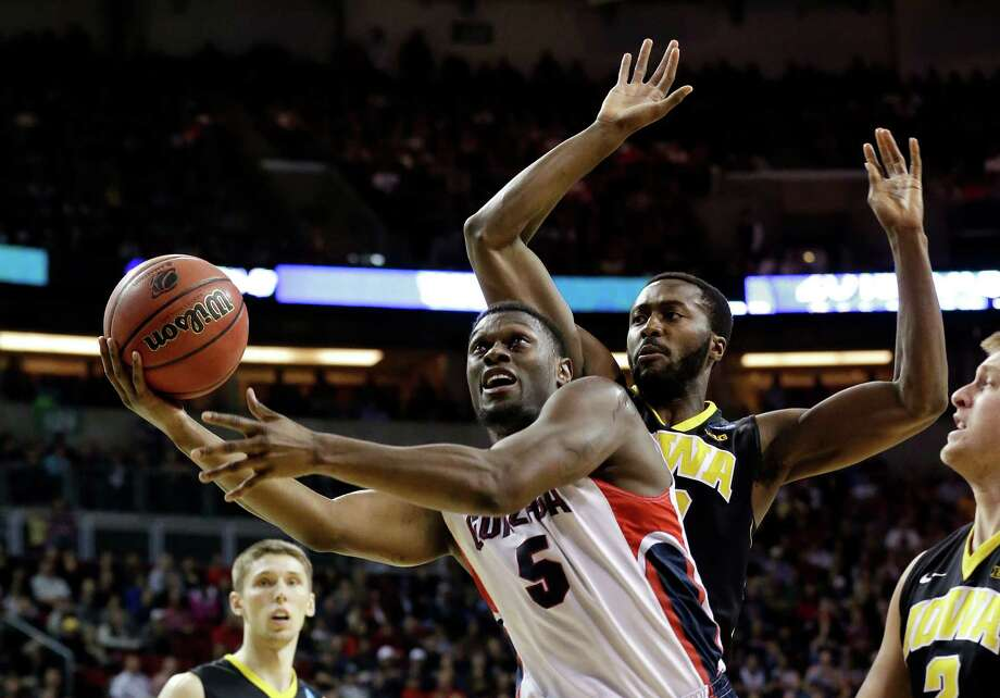 Gonzaga's Gary Bell Jr. (5) shoots as Iowa's Gabriel Olaseni defends during the first half of an NCAA tournament college basketball game in the Round of 32 in Seattle, Sunday, March 22, 2015. (AP Photo/Elaine Thompson) Photo: Elaine Thompson, Associated Press / AP