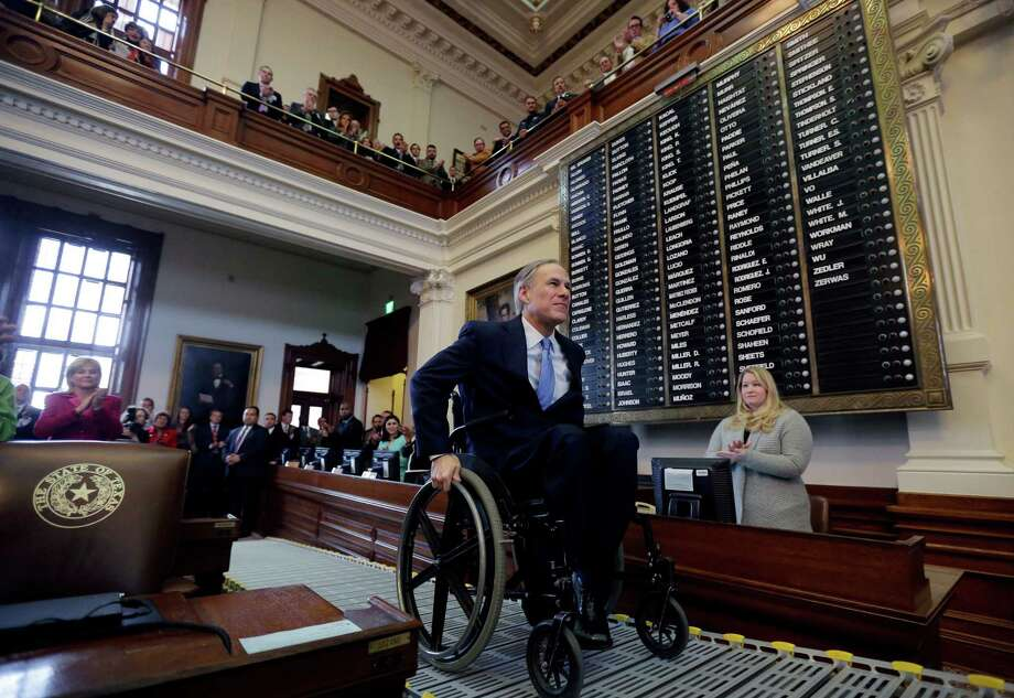 In this Feb. 17, 2015 file photo, Texas Gov. Greg Abbott arrives at the House Chamber to deliver his State of the State address to a joint session of the House and Senate, Tuesday, Feb. 17, 2015, in Austin, Texas. Abbott told lawmakers that roads, education and border security are the biggest issues facing Texans. Abbott's physical limitations provide more exposure to the difficulties faced by disabled Americans, and the new governor could be an asset to organizations pressing for changes to ease the public lives of the disabled in Texas and elsewhere. (AP Photo/Eric Gay) Photo: Eric Gay, STF / AP