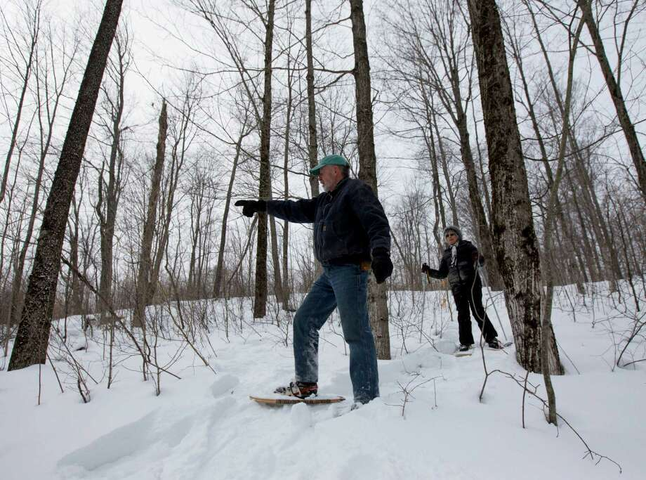 In this Thursday, Feb. 26 photo, Dev Kernan and his wife Karen Butler snowshoe on family property along the proposed path of the Constitution Pipeline in Harpersfield, N.Y. The 124-mile Constitution Pipeline will likely bring some relief from relatively high natural gas prices to residents of New York City and New England, but it will also bring anguish to many landowners in the wooded hills and valleys in its path. It will slash a mile-long gash through a pristine forest tended by the Kernan family for seven decades.  (AP Photo/Mike Groll)  ORG XMIT: NYMG201 Photo: Mike Groll / AP