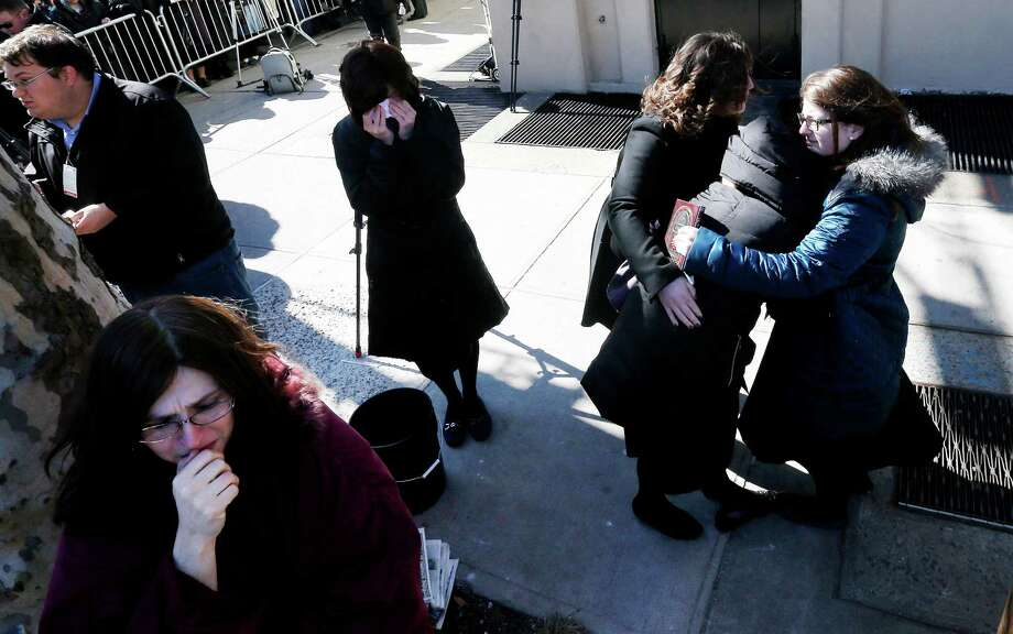 A woman is consoled as others cry as vehicles carrying the remains of the seven siblings killed in a house fire depart after funeral services, Sunday, March 22, 2015, in the Brooklyn borough of New York. The siblings, ages 5 to 16, died early Saturday when flames engulfed the Sassoon family home in the Midwood neighborhood of Brooklyn. Investigators believe a hot plate left on a kitchen counter set off the fire that trapped the children and badly injured their mother and another sibling. (AP Photo/Julio Cortez) ORG XMIT: NYJC113 Photo: Julio Cortez / AP