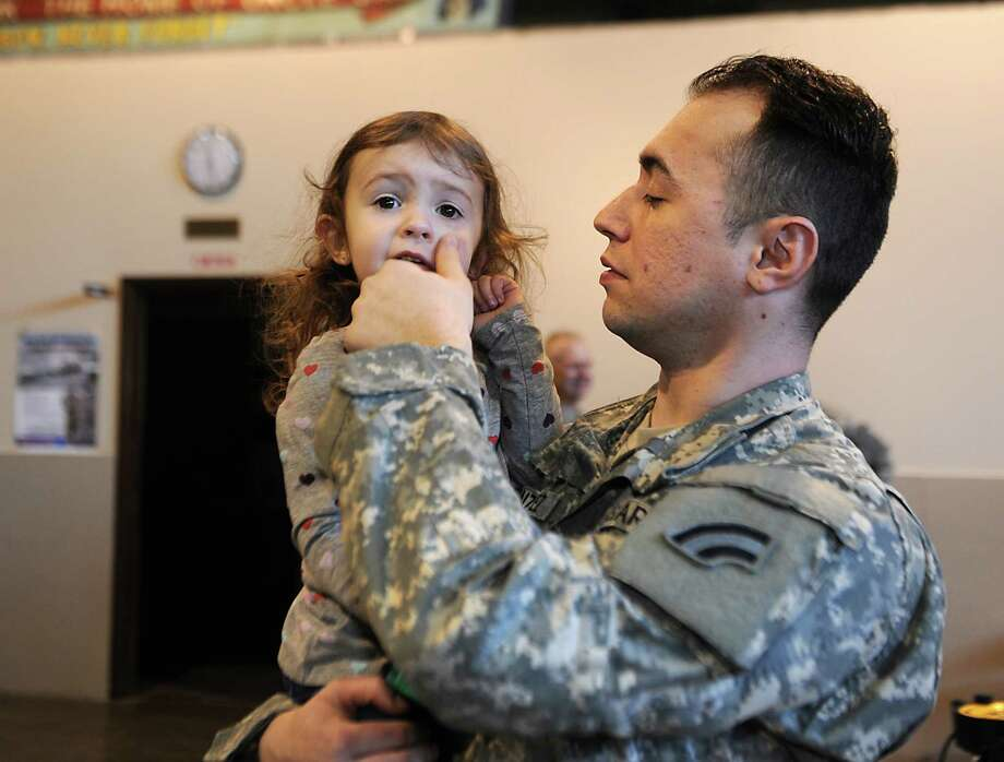 Sgt. Raymond Gonzalez of Green Island wipes the cheek of his daughter Ellie, 2, during a deployment ceremony at the 42nd Infantry Division headquarters on Sunday, March 22, 2015 in Troy, N.Y. Fifty-six New York Army National Guard Soldiers are slated to deploy to the Guantanamo Bay Naval Base in Cuba in April. (Lori Van Buren / Times Union) Photo: Lori Van Buren / 00031137A
