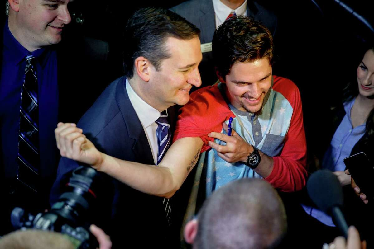 Sen. Ted Cruz, R-Texas, center, poses for a photograph with a member of the audience who has