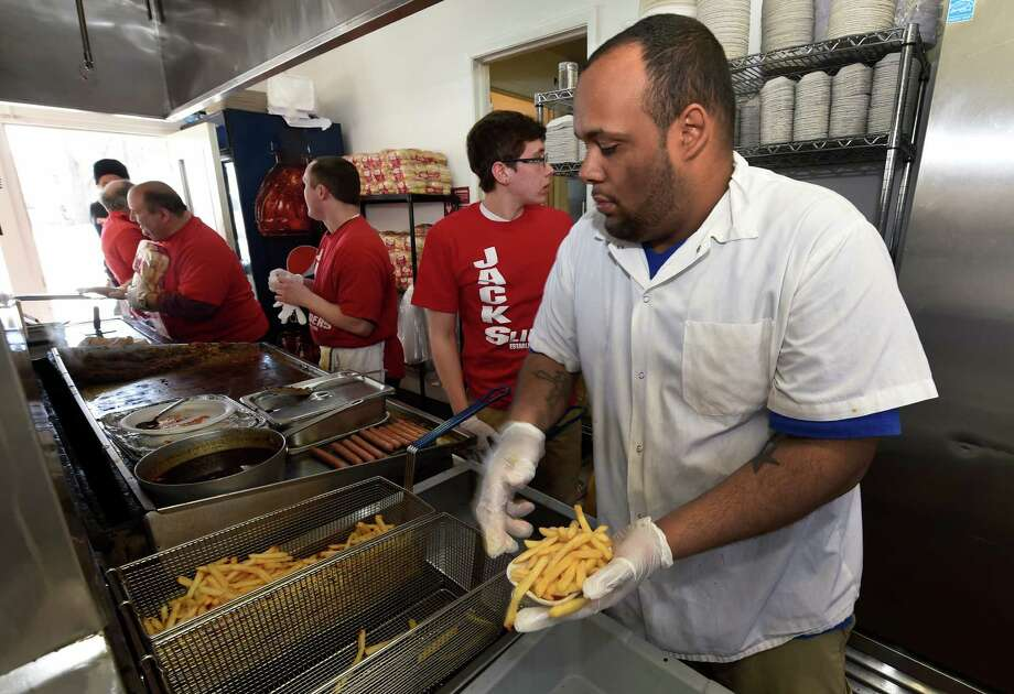Trevor Carter loads french fries at Jack's Drive In as they open for the 77th year Monday morning March 23, 2015 in Troy, N.Y. (Skip Dickstein/Times Union) Photo: SKIP DICKSTEIN / 00031141A