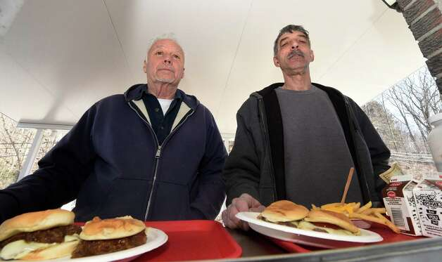 Customers Jimmy Fahey, left, and Rich Gregware received their burgers at the window of Jack's Drive In on the 77th opening day of the burger shop Monday morning, March 23, 2015, in Troy, N.Y.(Skip Dickstein/Times Union) Photo: SKIP DICKSTEIN / 00031141A