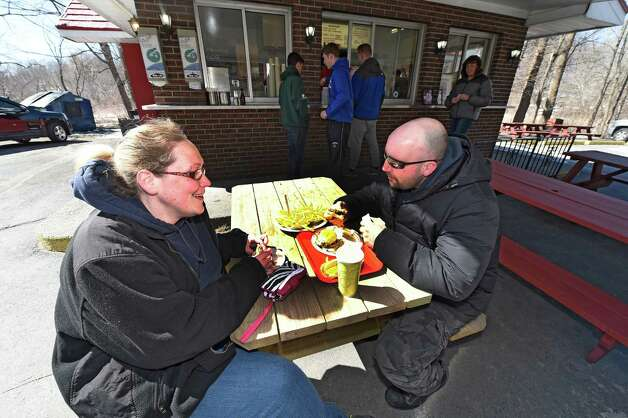Julie Crossman and Dennis Recore Jr. brave the cold to enjoy a burger lunch on the 77th opening day at Jack's Drive In Monday morning, March 23, 2015, in Troy, N.Y. (Skip Dickstein/Times Union) Photo: SKIP DICKSTEIN / 00031141A