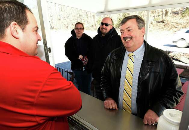 Troy Police Deputy Chief Richard McAvoy, right, orders lunch from Albert Deeb at Jack's Drive In on  the 77th opening day Monday morning March 23, 2015 in Troy, N.Y. (Skip Dickstein/Times Union) Photo: SKIP DICKSTEIN / 00031141A