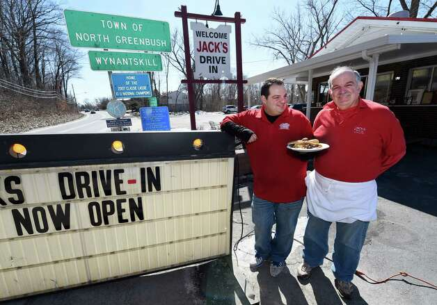Albert Deeb, left offers his dad Joe Deeb a dog in front of Jack's Drive In as they open for the 77th year Monday morning, March 23, 2015, in Troy, N.Y.          (Skip Dickstein/Times Union) Photo: SKIP DICKSTEIN / 00031141A