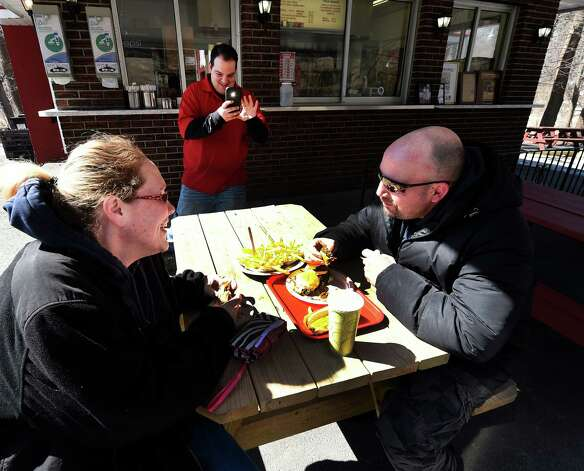 Co-owner Albert Deeb makes an image of Julie Crossman and Dennis Recore Jr. as they brave the cold to enjoy a burger lunch on the 77th opening day at Jack?s Drive In Monday morning, March 23, 2015, in Troy, N.Y. (Skip Dickstein/Times Union) Photo: SKIP DICKSTEIN / 00031141A