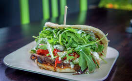 The Arrogant Greek sandwich ($7, or $9 with beef), at Spinnerie on Polk Street is thinly sliced tri-tip slathered in yogurt and pickled onions, pressed onto arugula and wrapped in a soft U of whole-wheat yogurt flatbread.