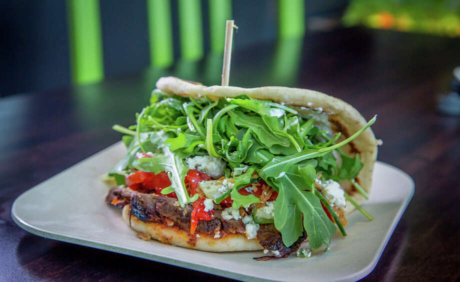 The Arrogant Greek sandwich ($7, or $9 with beef), at Spinnerie on Polk Street is thinly sliced tri-tip slathered in yogurt and pickled onions, pressed onto arugula and wrapped in a soft U of whole-wheat yogurt flatbread. Photo: John Storey / Special To The Chronicle / ONLINE_YES