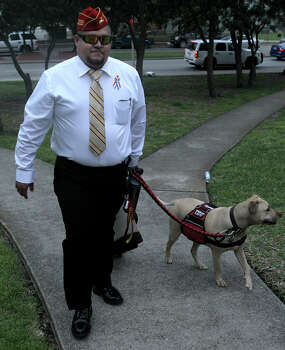 Juan Alonzo Miranda walks with his service dog, Goldie, to the courthouse March 16 for the first day of the trial. Photo: John Davenport /San Antonio Express-News / ©San Antonio Express-News