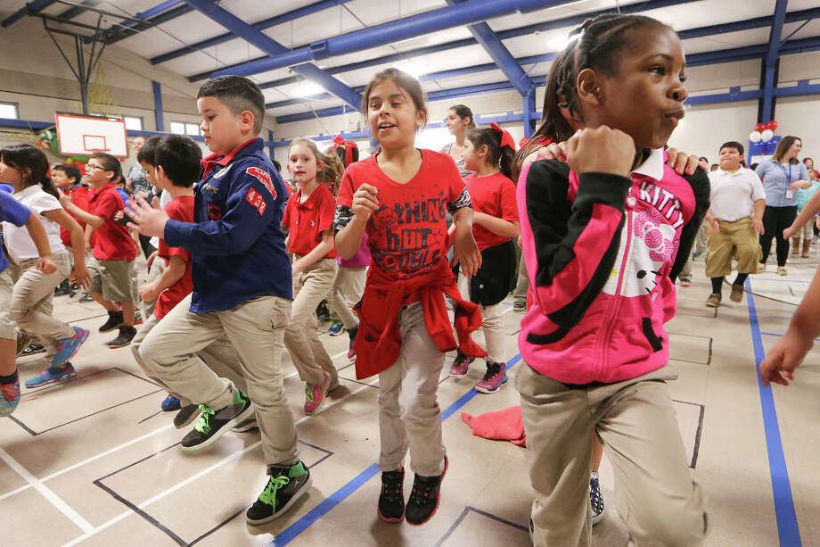 "Cameran Lassiter (front, from right), 8, Madison Cardenas, 8 and Jeramiah Villarreal, 7, exercise with other students in the gym as Collins Garden Elementary School, 167 Harriman Place, celebrated Heroes for Health Day on Thursday, March 19, 2015. The event, organized by the Bexar County School Boards Coalition and ""Go Public,"" stressed the importance of health and fitness for kids. MARVIN PFEIFFER/ mpfeiffer@express-news.net Photo: Marvin Pfeiffer /San Antonio Express-News / Express-News 2015"