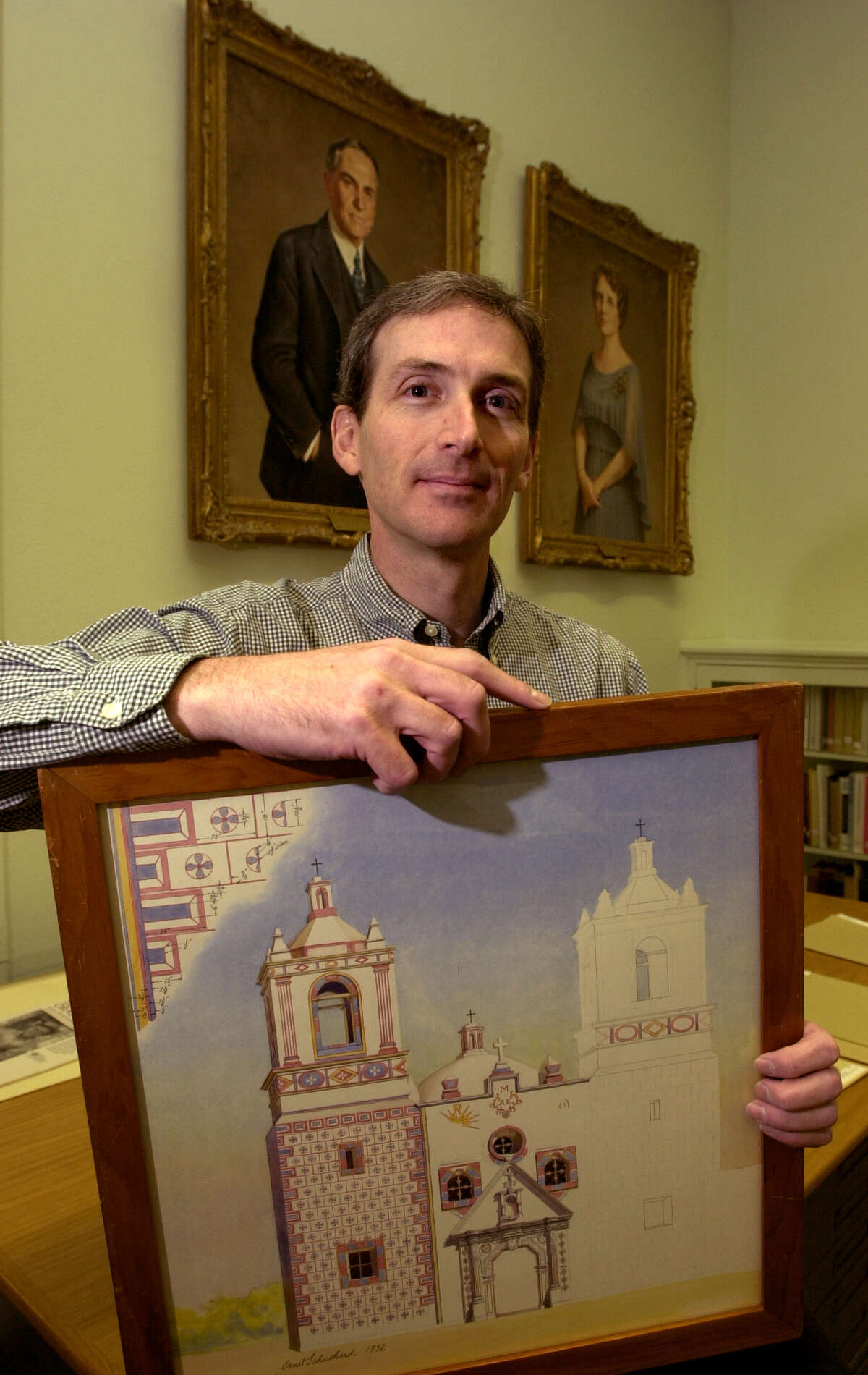 Warren Stricker, archivist at the DRT Library, shows a circa-1932 rendering by Ernst Schuchard depicting frescoes on the facade of Mission Concepcion, in preparation for the library's 50th anniversary in 2000. In the background are paintings of John and Sally Beretta, whose financial contributions started the library, now called the Alamo Research Center.