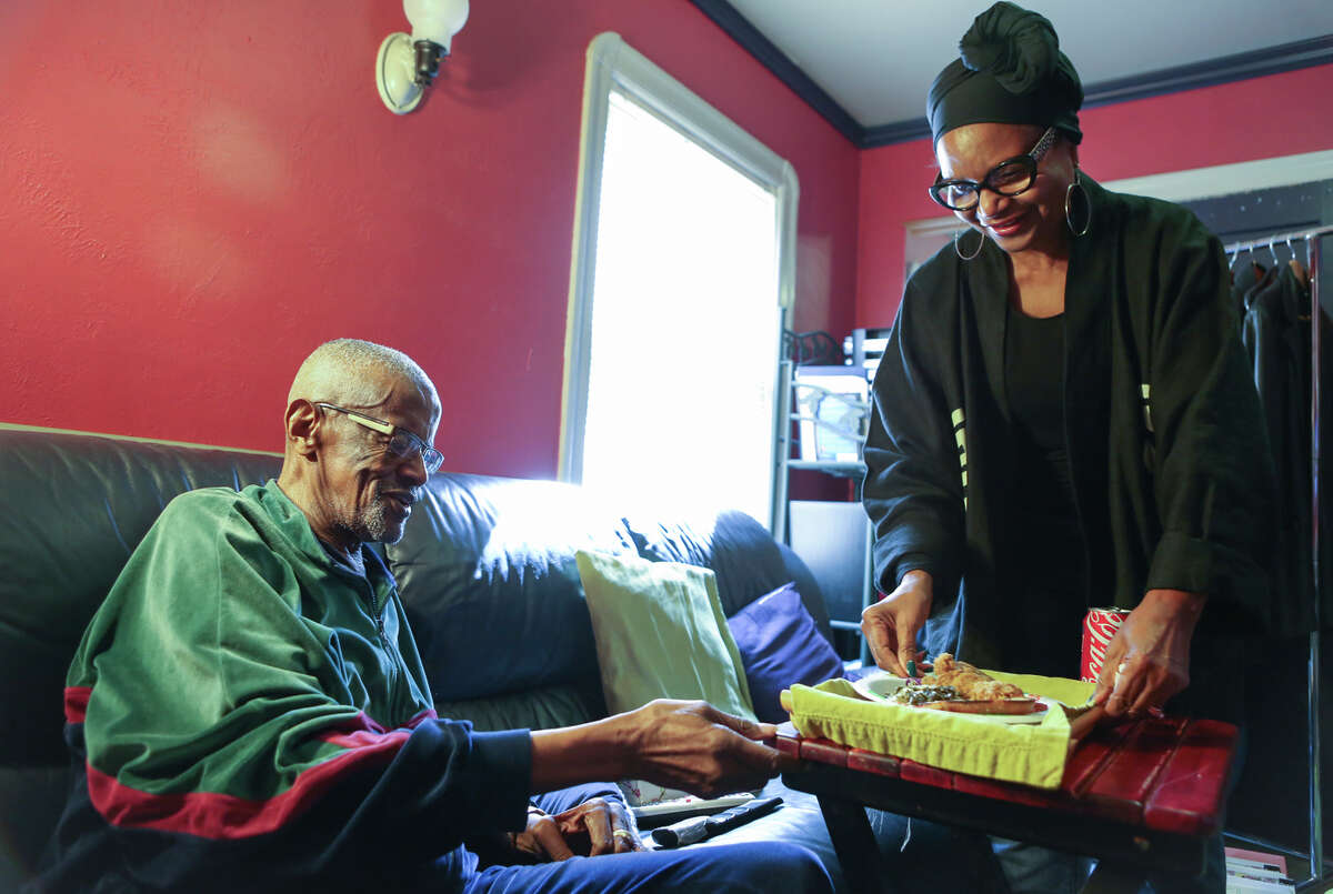 """Chris Mason of Oakland serves lunch to her husband, Nathaniel. """"He functions well but ... it's like taking care of a child,"""" she says of the 85-year-old, diagnosed with Alzheimer's in 2013."""