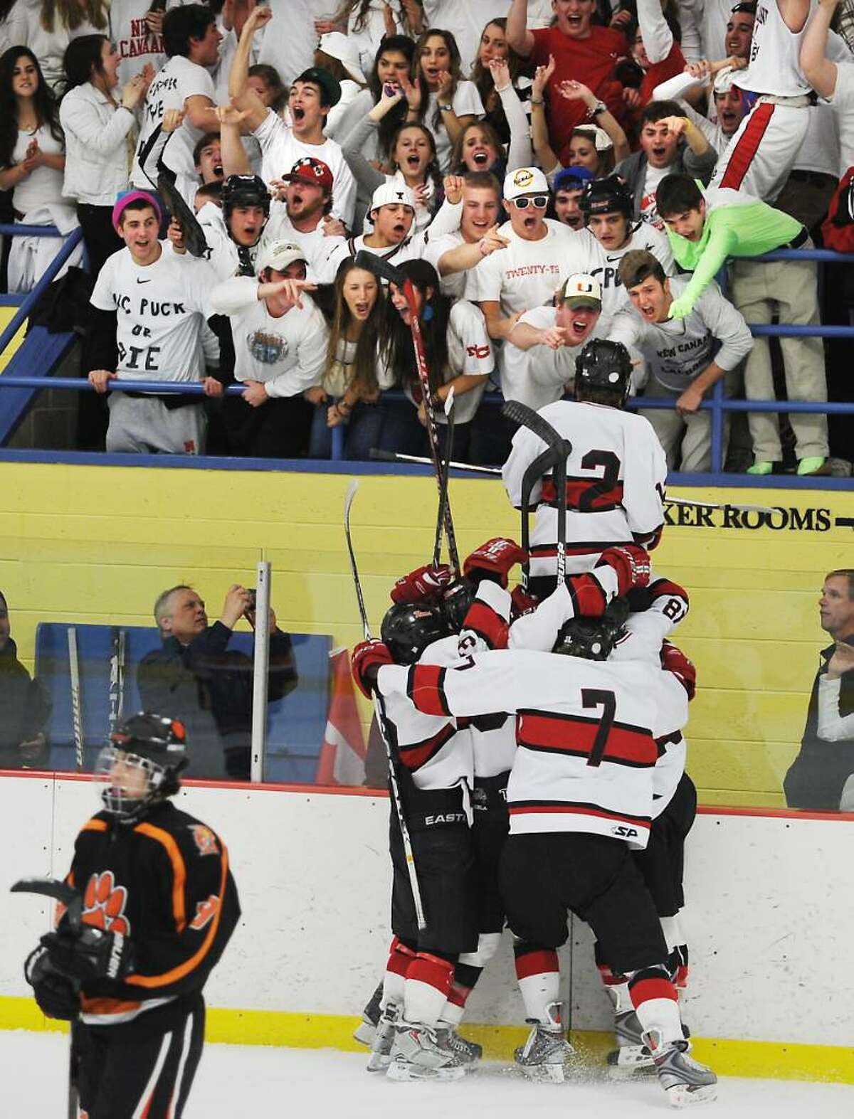 New Canaan's Tim Robustelli jumps up to the fans as he scores in the second period against Ridgefield in the FCIAC boys hockey championship game at Terry Conners Rink in Stamford, Conn. on Saturday, March 6, 2010.