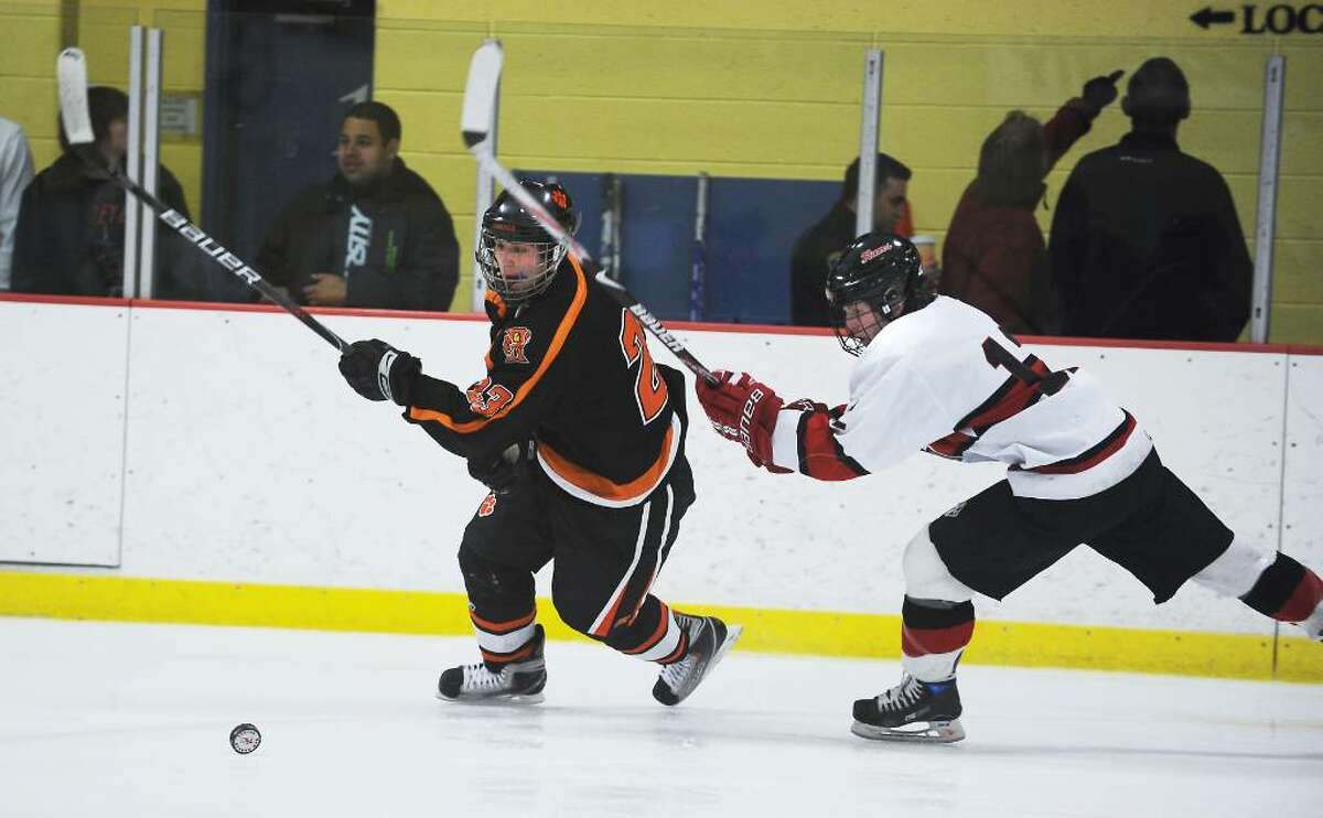 Ridgefield's Duncan Morrissey and New Canaan's Tim Robustelli battle for control of the puck in the FCIAC boys hockey championship game at Terry Conners Rink in Stamford, Conn. on Saturday, March 6, 2010.