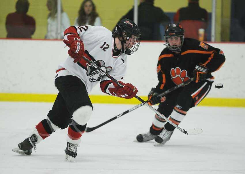 New Canaan's Tim Robustelli passes the puck against Ridgefield's Danny McMullan in the FCIAC boys hockey championship game at Terry Conners Rink in Stamford, Conn. on Saturday, March 6, 2010.
