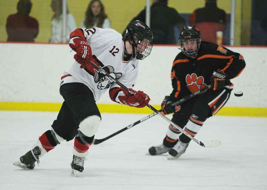 New Canaan's Tim Robustelli passes the puck against Ridgefield's Danny McMullan in the FCIAC boys hockey championship game at Terry Conners Rink in Stamford, Conn. on Saturday, March 6, 2010. Photo: Kathleen O'Rourke / Stamford Advocate