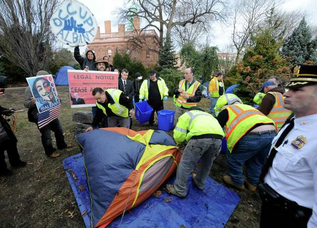 Under the watchful eye of the Albany Police members of the Albany Department of General Services remove tents and anything related to the encampment of Occupy Albany  Dec. 22, 2011, at Academy Park in Albany, N.Y.  (Skip Dickstein / Times Union archive Photo: SKIP DICKSTEIN