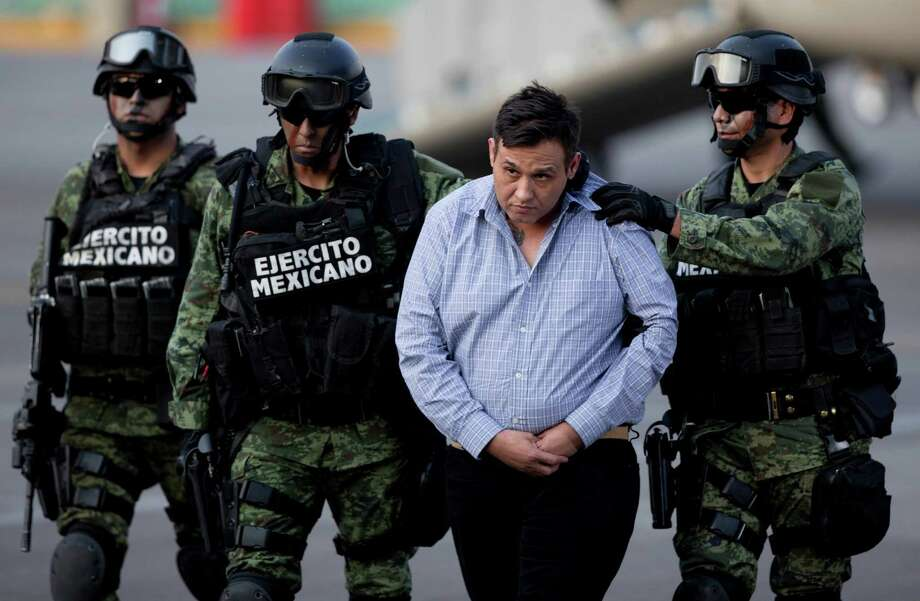 "Soldiers escort a man who authorities identified as Omar Trevino Morales, alias ""Z-42,"" leader of the Zetas drug cartel, as he is moved from a military plane to a military vehicle at the Attorney General's Office hangar in Mexico City, Wednesday, March 4, 2015. An official who was not authorized to be quoted by name because of government policy, said Morales was arrested on Wednesday in a pre-dawn raid in San Pedro Garza Garcia, a wealthy suburb of the northern city of Monterrey. (AP Photo/Eduardo Verdugo) Photo: Eduardo Verdugo, Eduardo Verdugo/AP / AP"