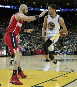 Stephen Curry (30) passes behind the back while guarded by Marcin Gortat (4) in the first half of the Golden State Warriors game against the Washington Wizards at Oracle Arena in Oakland, Calif, on Monday, March 23, 2015.