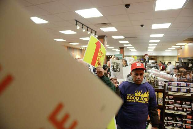 Minimum wage advocates occupy the Dunkin' Donuts on the first floor of the Capitol during a rally in support of increasing the state wage to $15 per hour Monday, March 23, 2015, at the Capitol in Albany, N.Y. (Will Waldron/Times Union) Photo: WW / 00031142A