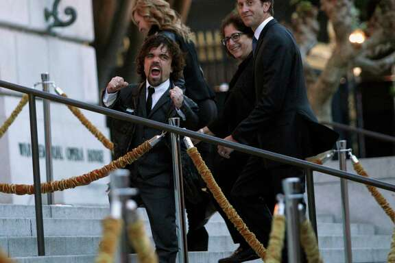 Peter Dinklage, who plays Tyrion Lannister in the Game of Thrones television series, cheers and pumps up the crowd at the season 5 premiere at the War Memorial Opera House, Monday, March 23, 2015, in San Francisco, Calif.