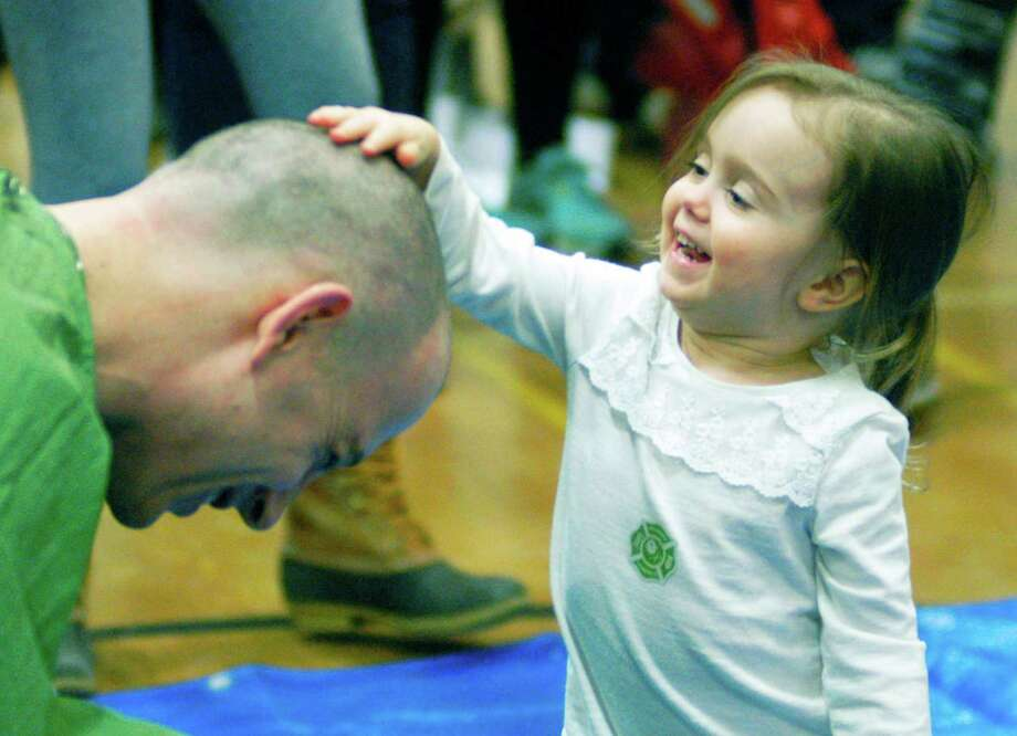 Little Madeline Balanda, 3, seemingly approves of the new hairdo sported by her dad, assistant principal Marc Balanda, during New Milford's High School's St. Baldrick's Foundation head-shaving fundraiser, March 16, 2015 Photo: Norm Cummings / The News-Times