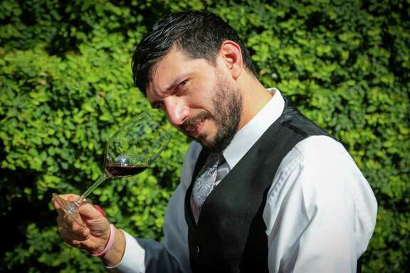 Tony Mandola's restaurant's  Ash Iraqui with a glass of Archery Summit Willamette Valley Pinot Noir, Wednesday March 18, 2015. (Billy Smith II / Houston Chronicle)